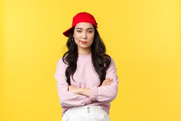 Menschen emotionen, lifestyle-freizeit- und schönheitskonzept. ernsthaft aussehende selbstbewusste asiatische frau in roter mütze, cool und frech aussehend, kreuzarme brust entschlossen, stehend gelber hintergrund.