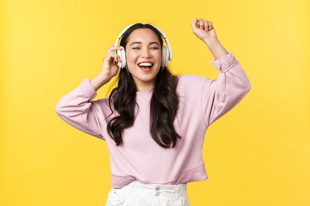 Menschen emotionen, lifestyle-freizeit- und schönheitskonzept. fröhliche hübsche asiatische frau in drahtlosen kopfhörern, die musik hört, aufgeregt mit geschlossenen augen und glücklichem lächeln tanzt, lieblingslied hört.