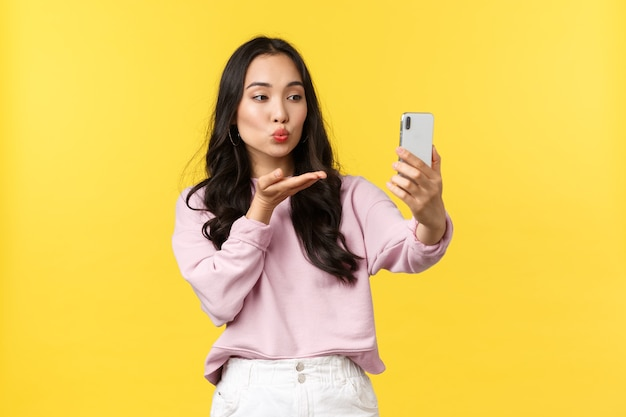 Menschen emotionen, lifestyle-freizeit- und schönheitskonzept. stilvolles und flirtendes asiatisches mädchen, das fotos für soziale medien macht, selfie macht, luftkuss an die smartphone-kamera sendet, gelber hintergrund steht.