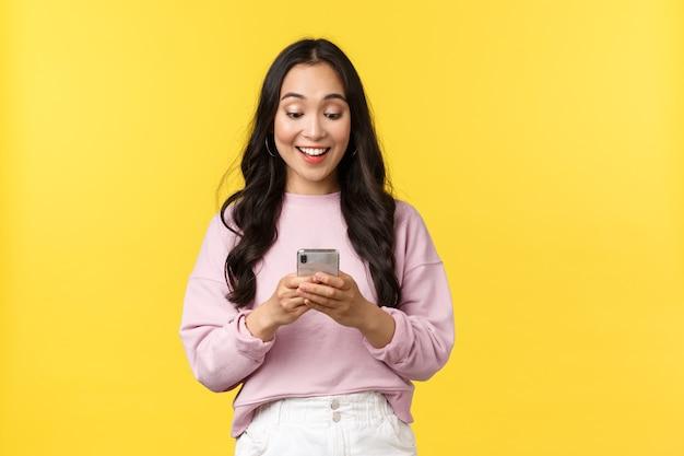 Menschen emotionen, lifestyle-freizeit- und schönheitskonzept. überraschtes und glückliches asiatisches mädchen erhält großartige nachrichten über das telefon, schaut mit erstauntem lächeln auf das mobile display und jubelt auf gelbem hintergrund.