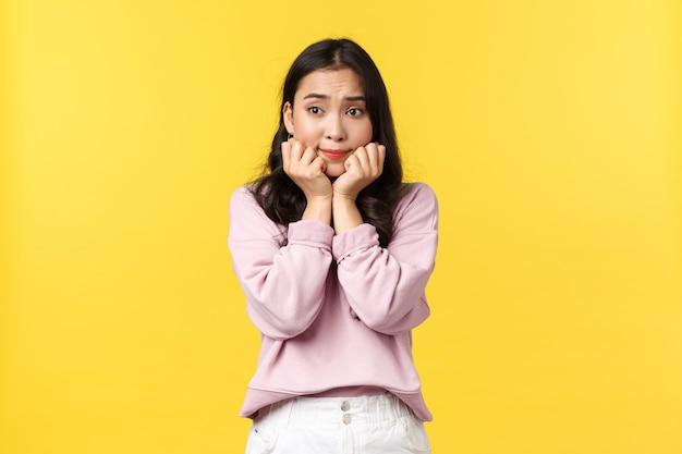 Menschen emotionen, lifestyle und modekonzept. besorgtes nachdenkliches asiatisches mädchen, das die hände ans kinn gedrückt hält und verträumt wegschaut, sich vor einem wichtigen interview nervös fühlt, gelber hintergrund