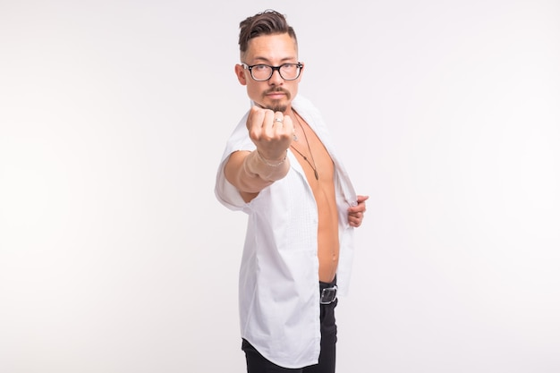 Menschen, emotionen und gestenkonzept - hübscher mann im weißen hemd, das seine faust auf weiß zeigt