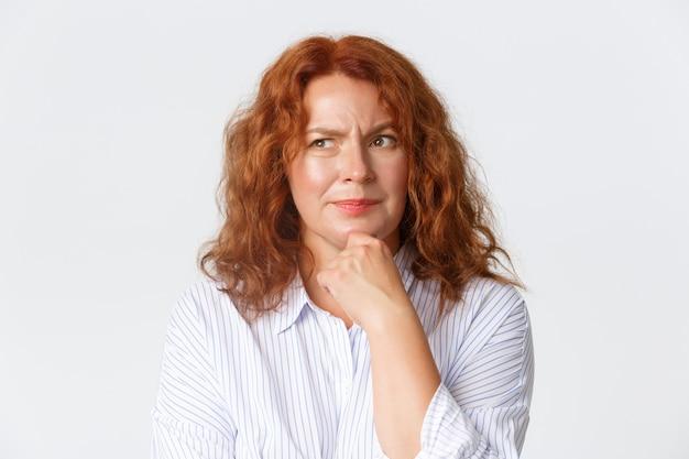 Menschen, emotionen und lifestyle-konzept. nahaufnahme der nachdenklichen rothaarigen mutter mittleren alters, der frau, die entscheidung trifft, die obere linke ecke schaut und denkt, über entscheidung nachdenkt, weiße wand.
