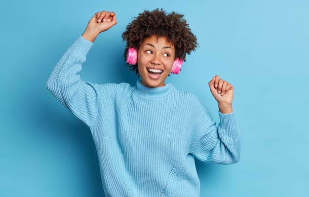Menschen entspannung aktivität glück konzept. zufriedene dunkelhäutige frau mit afro-haar bewegt sich zur musik trägt drahtlose stereo-kopfhörer und lächelt fröhlich, breit gekleidet in einem lässigen pullover.