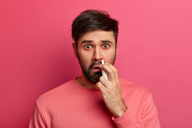 Menschen, erkältungssymptome und medikamentenkonzept. unglücklicher kranker mann verwendet nasentropfen, hat rhinitis und verstopfte nase, heilt krankheiten, leidet an allergischen reaktionen, fühlt sich unwohl. sinusitis-behandlung