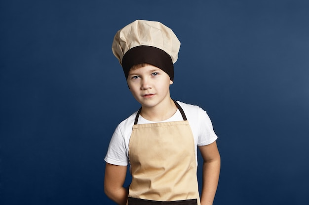 Menschen, essen, kochen, kochen, gastronomie und küchenkonzept. bild des hübschen selbstbewussten jugendlichen jungen mit den blauen augen, die im studio posieren, das weißes hemd, die schürze und die kochmütze tragen, abendessen kochend