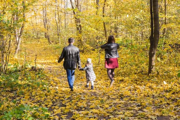 Menschen-, familien- und freizeitkonzept - glückliche familie mit tochter, die im herbstpark spazieren geht, rückansicht