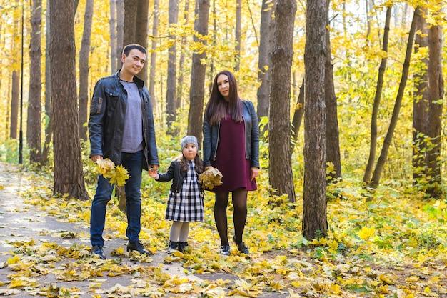 Menschen-, familien- und freizeitkonzept - glückliche familie mit tochter, die im herbstpark spaziert.