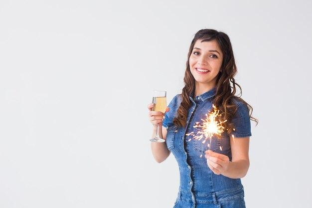 Menschen, feiern und feiertagskonzept - schöne frau mit wunderkerze und glas champagner auf weißem hintergrund mit kopienraum.