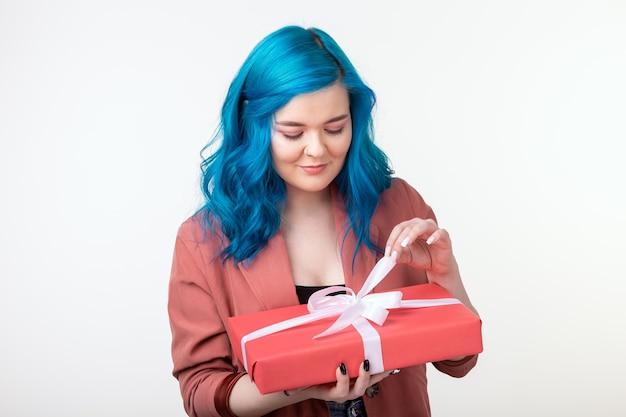 Menschen, feiertage und modekonzept - glückliche junge frau mit blauen haaren, die eine geschenkbox auf weißem hintergrund halten