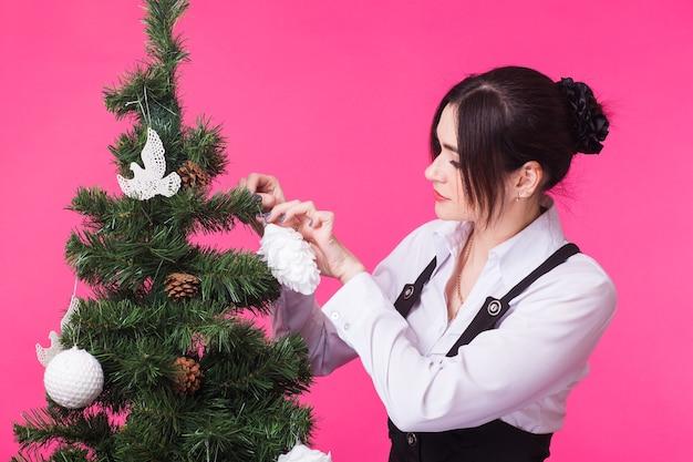 Menschen, feiertage und weihnachtskonzept - frau, die weihnachtsbaum auf rosa hintergrund verziert