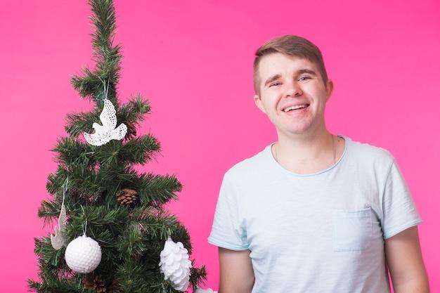 Menschen, feiertage und weihnachtskonzept - junger lächelnder mann nahe weihnachtsbaum auf rosa hintergrund