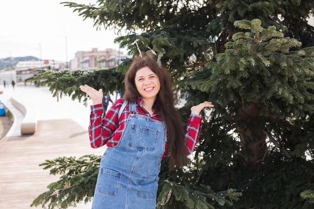 Menschen-, feiertags- und feierkonzept - junge frau, die weihnachtsbaum im freien verziert.