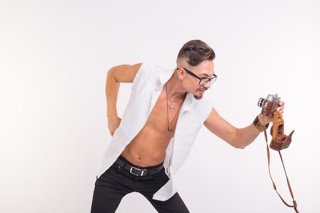 Menschen-, foto- und stilkonzept - glücklicher junger mann, der selfie mit alter fotokamera auf weißem hintergrund macht.