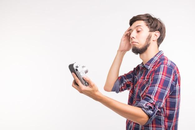 Menschen, fotograf und gestenkonzept - mann, der eine altmodische kamera verwendet, die durch die linse auf weißer oberfläche schaut