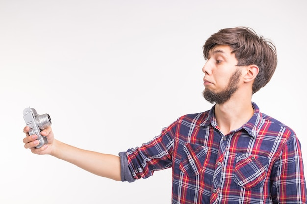 Menschen, fotograf und gestenkonzept - mann mit einer altmodischen kamera, die durch die linse auf weißem hintergrund schaut