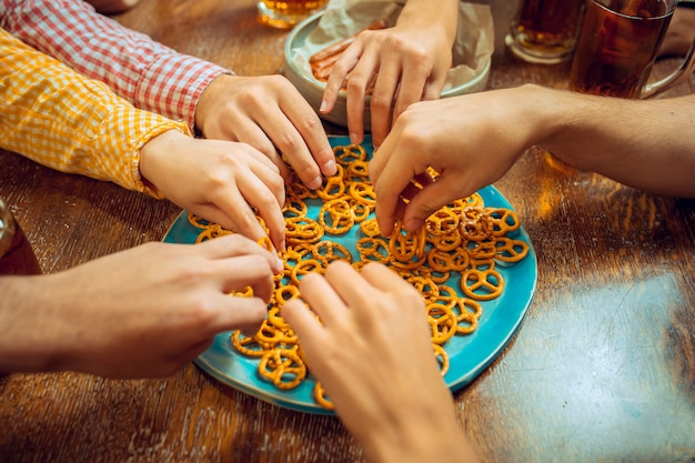 Menschen, freizeit, freundschaft und kommunikationskonzept. glückliche freunde trinken bier, reden und klirren an der bar oder im pub.