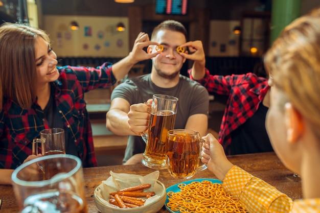 Menschen-, freizeit-, freundschafts- und kommunikationskonzept - glückliche freunde, die bier trinken, reden und an der bar oder in der kneipe klirren