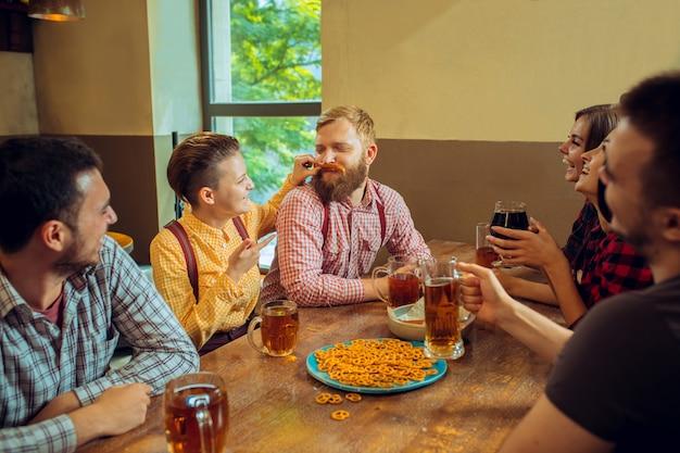 Menschen-, freizeit-, freundschafts- und kommunikationskonzept - glückliche freunde, die bier trinken, reden und gläser in der bar oder im pub anstoßen