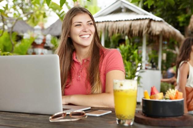 Menschen, freizeit, technologie und kommunikation. attraktive geschäftsfrau im urlaub mit einem laptop, die ihre e-mails abruft und freunde online über soziale netzwerke benachrichtigt