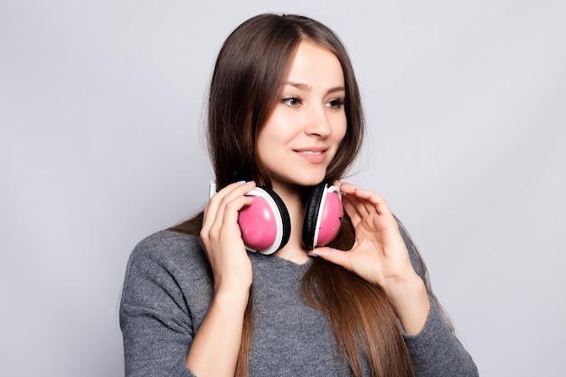 Menschen-, freizeit- und technologiekonzept - glückliche frau oder teenager-mädchen in kopfhörern, die musik vom smartphone hören und tanzen