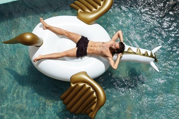 Menschen-, freizeit- und urlaubskonzept. außenaufnahme des attraktiven jungen kaukasischen mannes, der hemdlos auf riesigem luftbett liegt, während freie und glückliche momente seiner ferien in den tropen genießt