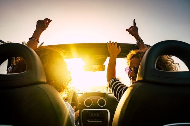 Menschen freude und fröhliches fahren und reisen für sommerferien und freizeitaktivitäten im freien mit cabrio auto lachen und tanzen wie verrückt