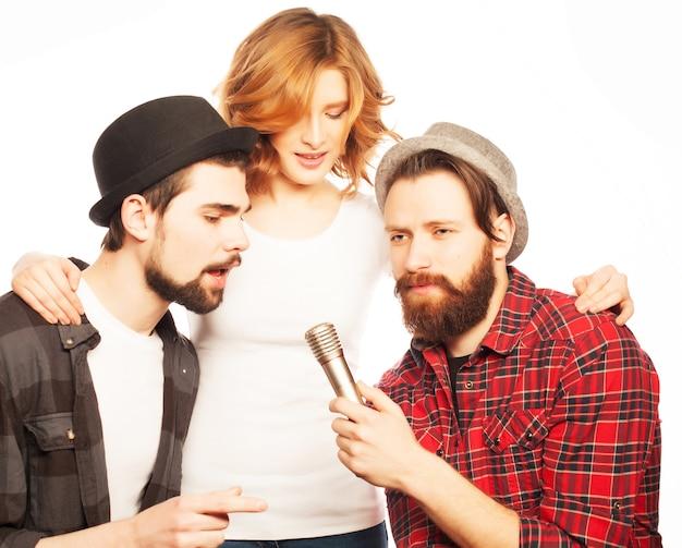 Menschen-, freundschafts- und freizeitkonzept: gruppe junger glücklicher freunde, die spaß am karaoke, hipster-stil haben. isoliert auf weiss.