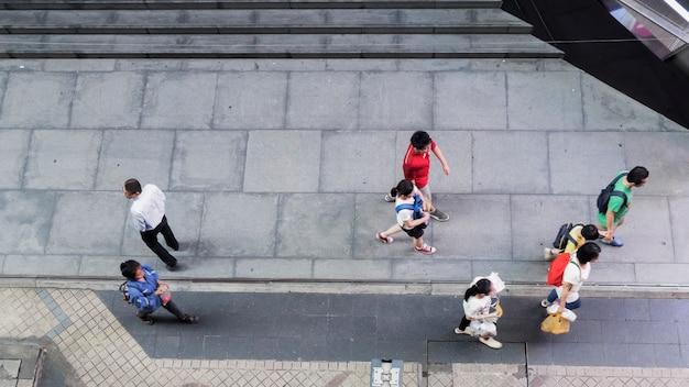 Menschen gehen auf dem fußgängerbetonpflaster in der geschäftsstadt.