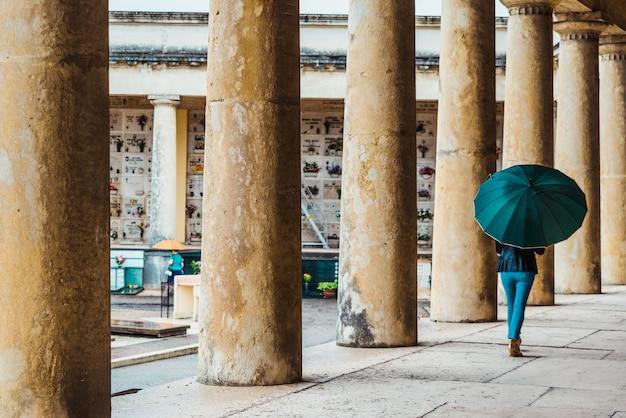Menschen gehen mit regenschirmen an einem regnerischen tag durch einen friedhof.