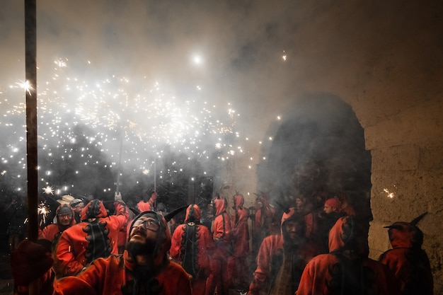 Menschen, gekleidet wie teufel, die mit pyrotechnik tanzen