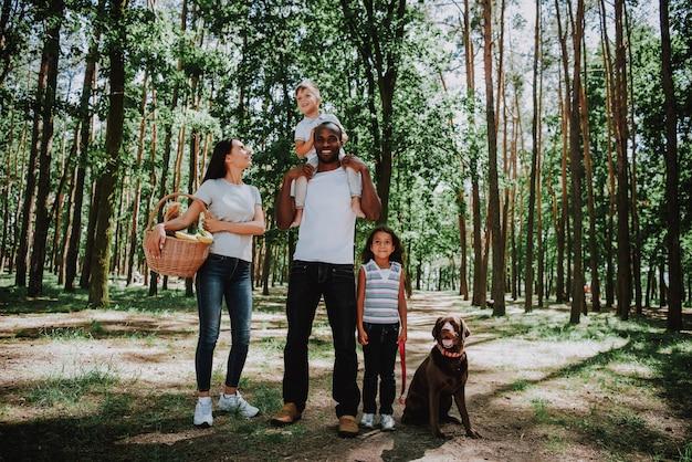 Menschen genießen spaziergang durch wald mit picknickkorb