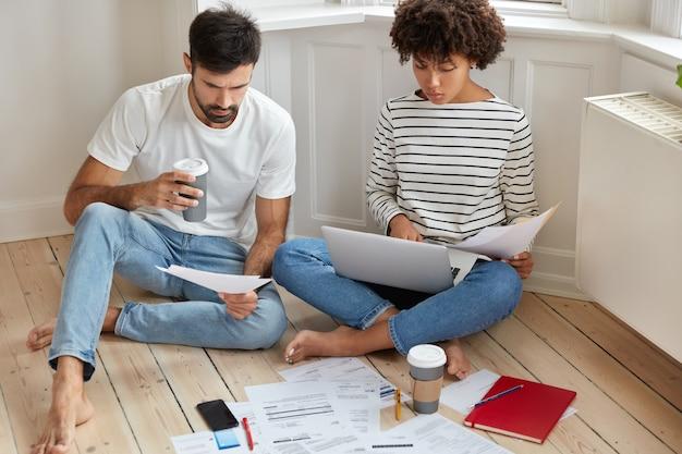 Menschen-, geschäfts- und arbeitskonzept. mitarbeiterinnen und mitarbeiter studieren die dokumentation und überlegen sich eine produktive strategie, um gewinne zu erzielen, posieren auf holzboden mit kaffee zum mitnehmen und schauen ernst