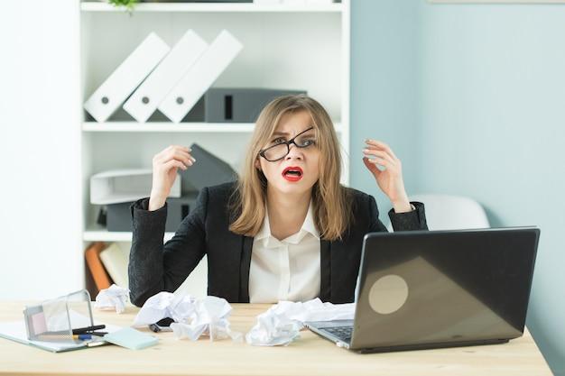 Menschen-, geschäfts- und emotionskonzept - frau mit verwirrtem ausdruck gekleidet im anzug im büro.