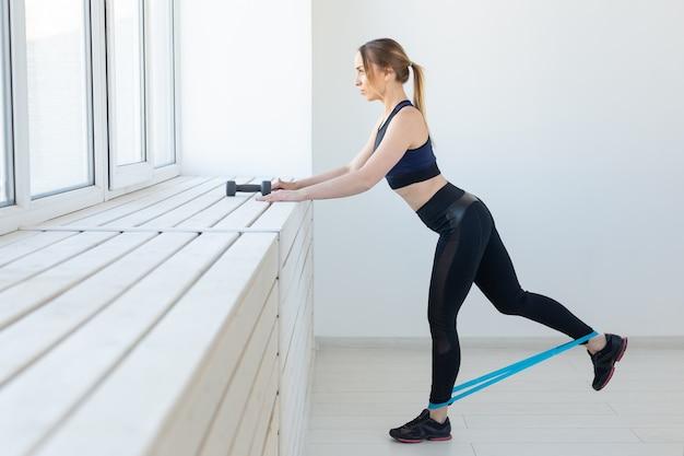 Menschen, gesund und sportlich konzept - fit frau in sportkleidung mit band hocken