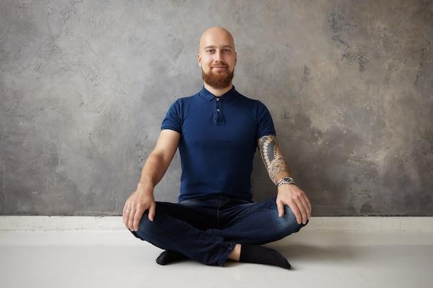 Menschen, gesundheit, yoga und lifestyle-konzept. horizontaler schuss des glücklichen positiven jungen bärtigen tätowierten yogis in der freizeitkleidung, die meditation drinnen praktiziert und mit gekreuzten beinen auf dem boden sitzt