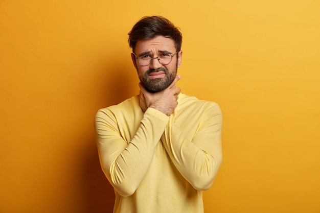 Menschen, gesundheitsprobleme konzept. unglücklicher frustrierter mann leidet unter halsschmerzen, berührt den nacken mit den händen, sieht unzufrieden aus, trägt eine runde brille und einen gelben pullover, hat asthmaanfall