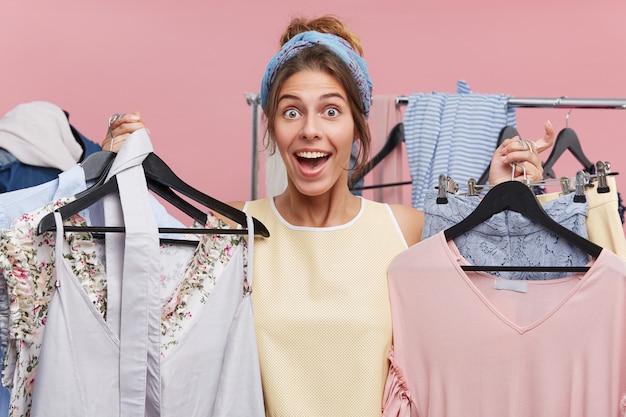 Menschen, glück, einkaufen, kaufkonzept. schöne frau, die gute laune hat, während sie viele kleiderbügel mit kleidern hält, freude fühlt, während sie sich auf neuen kauf oder modisches outfit freut