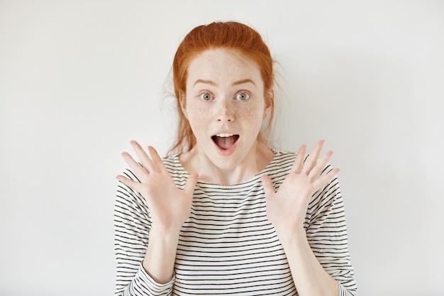 Menschen, glück und erfolgskonzept. schöne rothaarige studentin, die vor erstaunen und freude schreit und mit ihren händen gestikuliert, während sie die abschlussprüfungen mit hervorragenden noten besteht. körpersprache