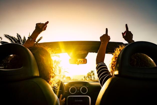 Menschen glücklich für reiseurlaub mit cabrio auto, das hände aufgibt und für die seesommerferien tanzt