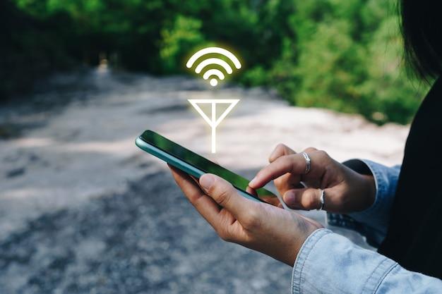 Menschen hand mit smartphone auf der suche nach signal-wlan außerhalb des stromnetzes kein stromraum oder im walddschungel.