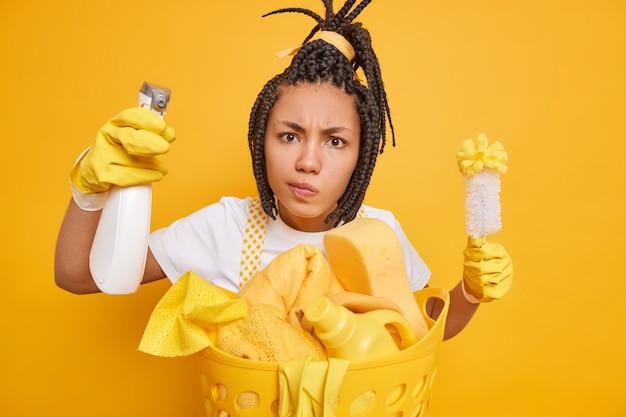 Menschen hausarbeit hausarbeit und reinigungskonzept. ernsthafte afro-amerikanerin hält pinsel und sprühflasche wischt staub in lässiger uniform, isoliert auf gelbem hintergrund, entfernt schmutz