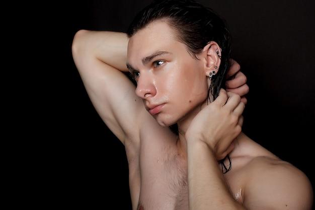 Menschen-, hautpflege- und schönheitskonzept - nasser junger mann mit langen schwarzen haaren auf einer schwarzen oberfläche