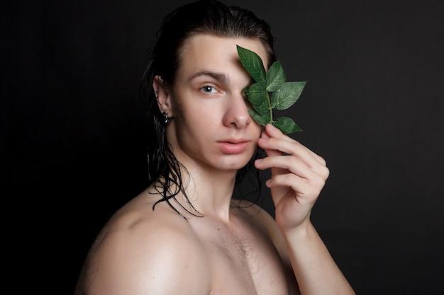 Menschen, hautpflege und schönheitskonzept - nasser junger mann mit langen schwarzen haaren auf schwarzem hintergrund. portraitmännchen mit rasierter brust. hautpflege für männer. zerrissener muskulöser gutaussehender mann auf schwarzem hintergrund