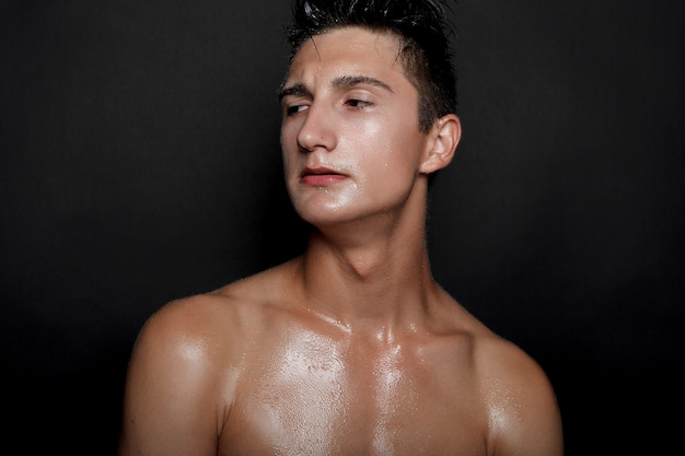 Menschen, hautpflege und schönheitskonzept - nasser junger mann mit schwarzem haar auf schwarzem hintergrund. portraitmännchen mit rasierter brust. hautpflege für männer. zerrissener muskulöser gutaussehender mann auf schwarzem hintergrund