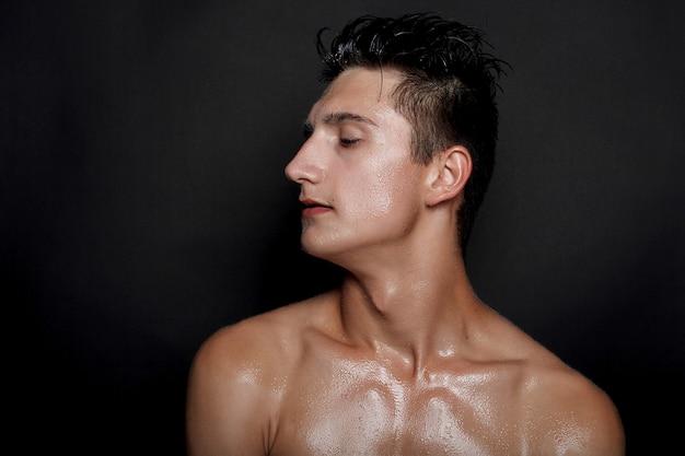 Menschen-, hautpflege- und schönheitskonzept - nasser junger mann mit schwarzem haar auf schwarzem hintergrund. portraitmännchen mit rasierter brust. hautpflege für männer. zerrissener muskulöser gutaussehender mann auf schwarzem hintergrund