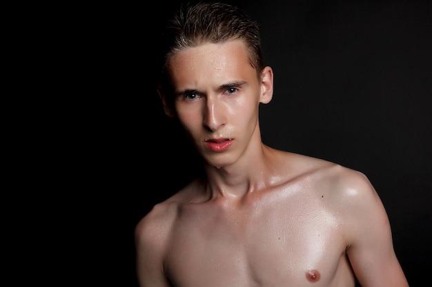 Menschen-, hautpflege- und schönheitskonzept - nasser junger mann mit schwarzen haaren auf einer schwarzen oberfläche