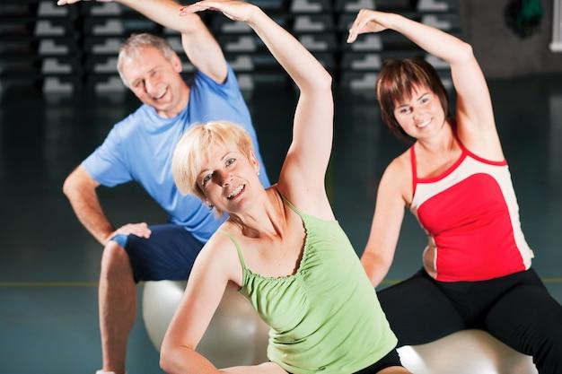 Menschen im fitnessstudio auf gymnastikball