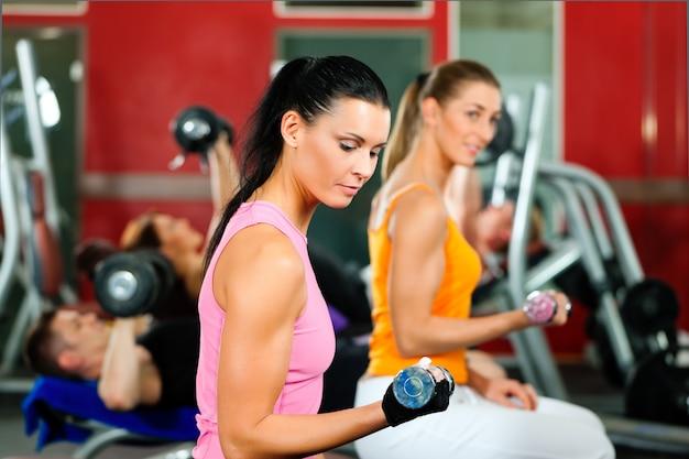 Menschen im fitnessstudio trainieren mit gewichten