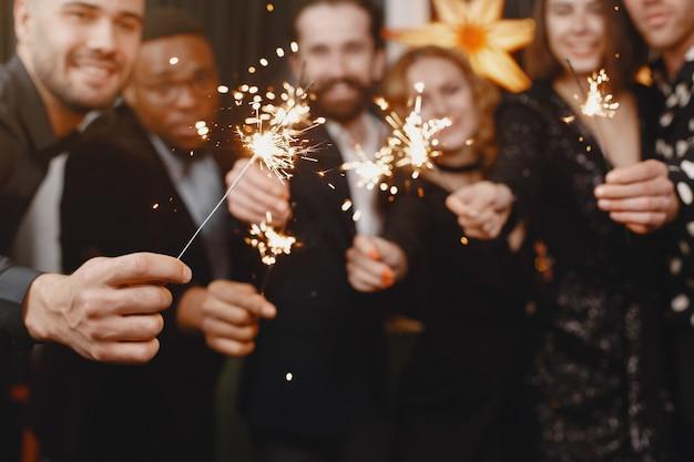 Menschen in einer christman-dekoration. mann im schwarzen anzug. gruppenfeiern neujahr. menschen mit bengalischen lichtern.